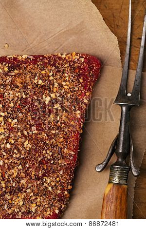 spice rubbed raw  beef, making jerky meat on wooden backdrop with vintage curving fork