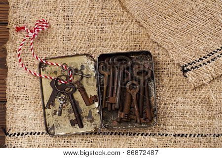 large rusty vintage metal keys in old tin in tin on old grain sacking linen Completely hand made  handwoven and homespun