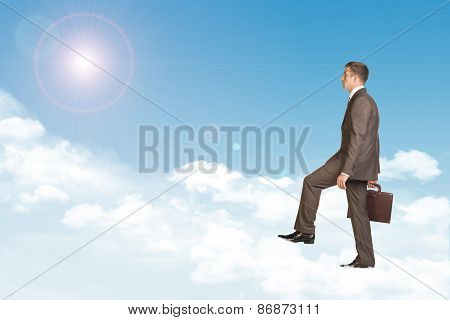 Businessman in suit with briefcase walking on cloud