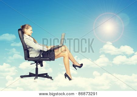 Woman sitting on office chair and holding open laptop, leaning back