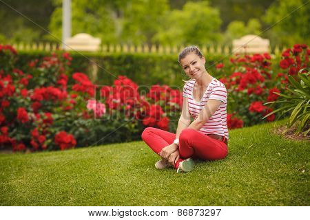 Beautiful young woman posing near rose garden.