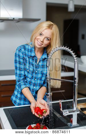 Girl washes strawberries in the kitchen.