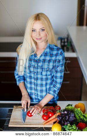 Beautiful housewife grinds the vegetables for the salad.