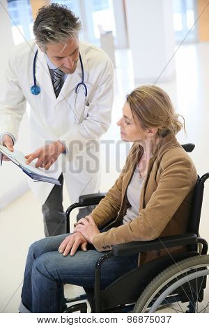 Doctor talking to woman in wheelchair after surgery