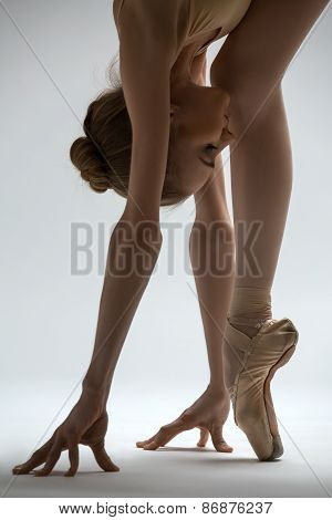 Fragile ballerina takes a deep slope forward, close-up photo