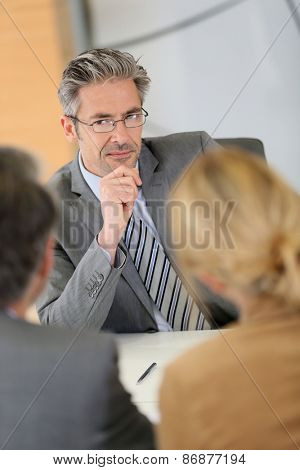 Consultant listening to clients in meeting