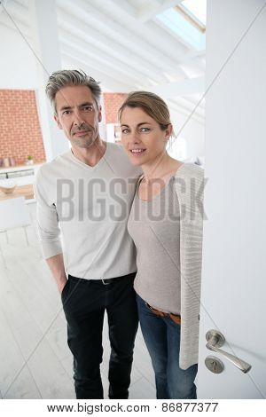 Mature couple opening door of their home