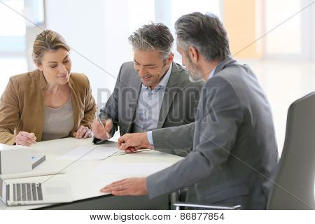 Mature couple signing construction contract in architect's office