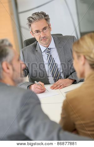 Mature couple signing contract in lawyer's office