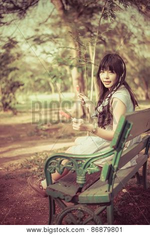 A Cute Asian Thai Girl Is Sitting On The Bench Holding An Ice Cream In Vintage Color