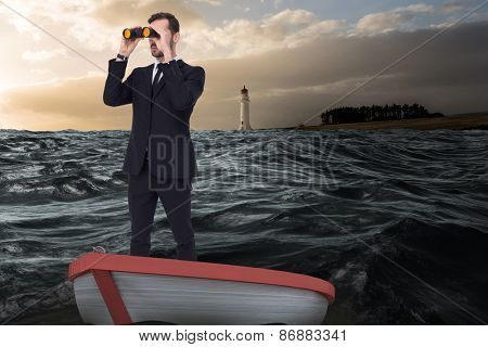 Businessman in boat with binoculars against stormy sea with lighthouse