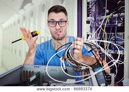 Portrait of confused it professional with screw driver and cables in front of open cpu against data center