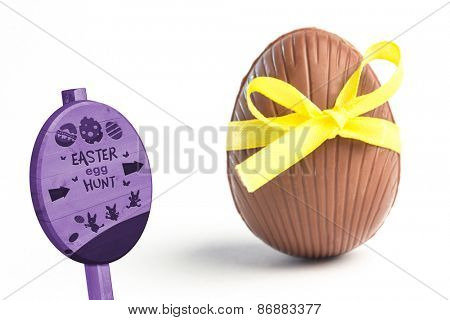 Easter egg hunt sign against chocolate easter egg in a yellow ribbon