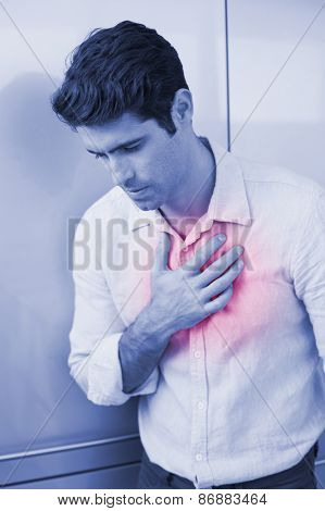 Casual young man with chest pain standing at home