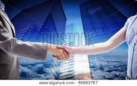 Handshake between two women against low angle view of skyscrapers
