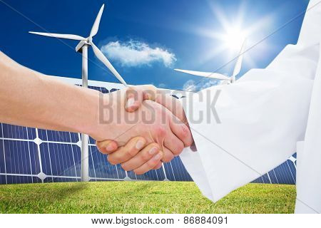 Closeup of a doctor and patient shaking hands against wind turbines and solar panels
