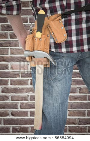 Cropped image of handyman wearing tool belt against red brick wall