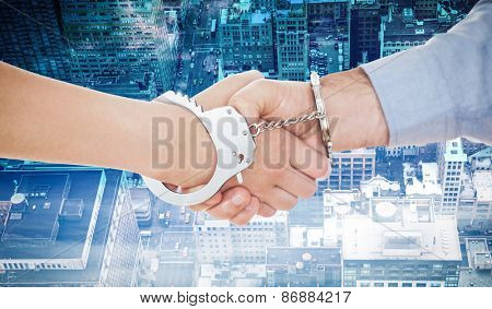 Handcuffed business people shaking hands against new york