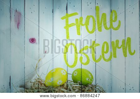 frohe ostern against white bunny beside nest of foil wrapped easter eggs