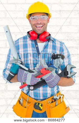 Portrait of smiling manual worker holding various tools against white wall