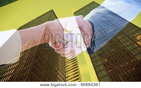Closeup of shaking hands after business meeting against skyscraper