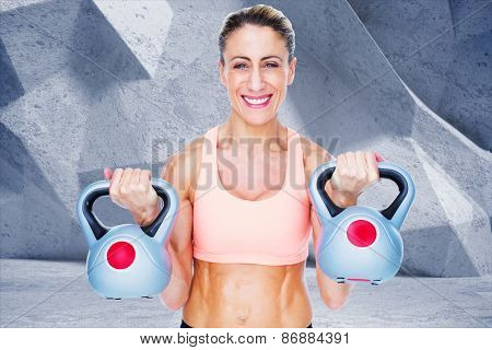 Smiling female crossfitter lifting kettlebells against grey angular background