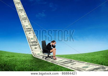 Worried businesswoman on swivel chair against green field under blue sky
