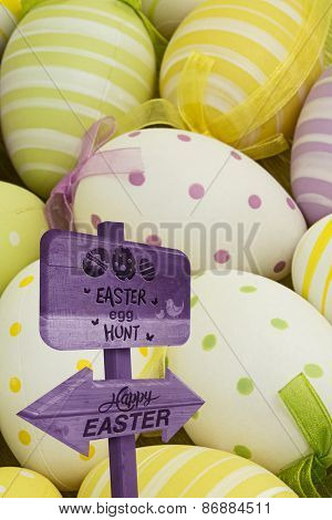 Easter egg hunt sign against easter eggs nestled together