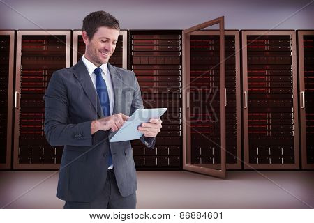 Businessman using his tablet pc against server towers