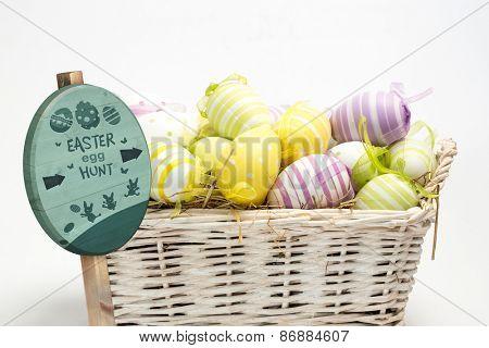 Easter egg hunt sign against easter eggs in straw