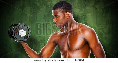 Serious fit shirtless young man lifting dumbbell against green paint splashed surface
