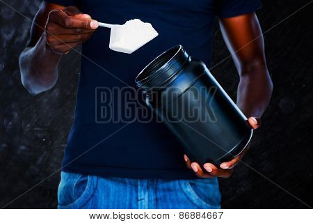 Mid section of man holding a scoop of protein mix against black background