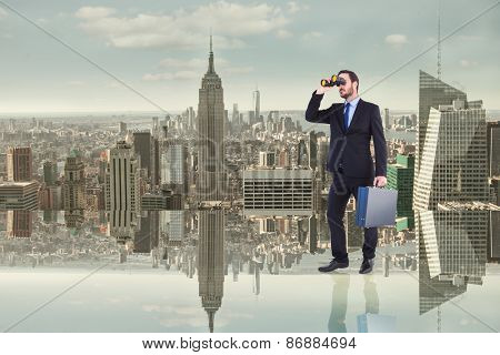 Businessman looking through binoculars holding briefcase against room with large window looking on city