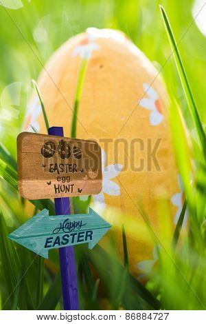 Easter egg hunt sign against easter egg wrapped in foil nestled in the grass