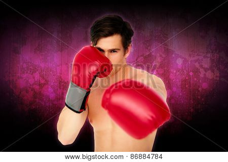Tough man wearing red boxing gloves punching to camera against dark background