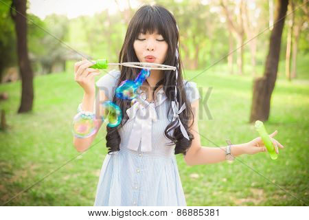 Cute Asian Thai Girl Is Blowing A Soap Bubbles In The Park