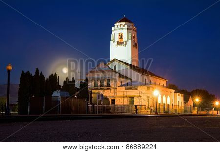 an old train depot with empty tracks at night with the moon rising behind