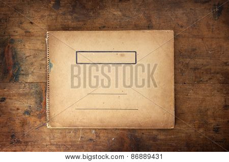 Cover of old 1950s - 1960s sketchbook or scrapbook on old well used wooden table or desk.