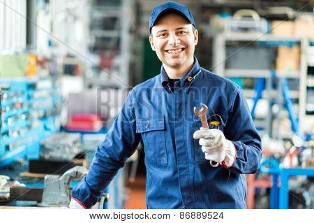 Auto mechanic smiling in his garage