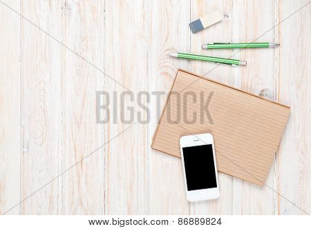 Office desk table with supplies and smartphone. Top view with copy space