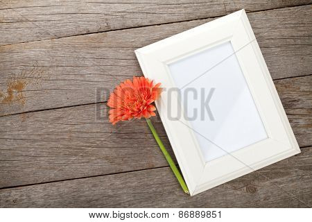 Blank photo frame and orange gerbera on wooden table background