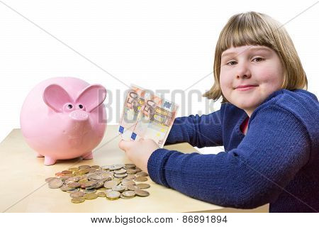 Young dutch girl showing euro money and piggy bank