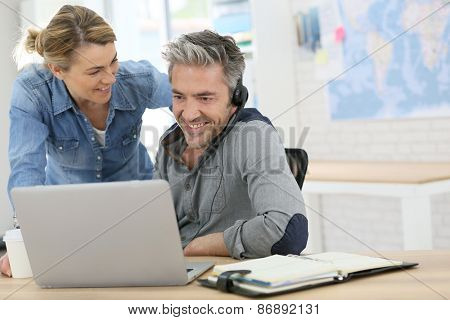 Colleagues in office working on laptop computer