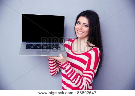 Smiling woman showing blank laptop display over gray background. Looking at camera