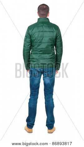 Back view of handsome man in blue windcheater looking. Standing young guy in jeans. Rear view people collection.  backside view of person.  Isolated over white background.