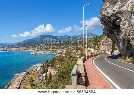 Scenic road under blue sky along Mediterranean sea coastline on French-Italian border.