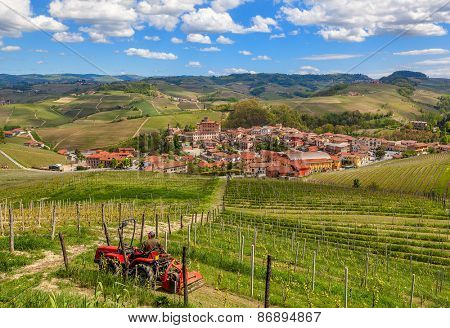 Small tractor among green vineyards and small town of Barolo on background in Piedmont, Northern Italy.