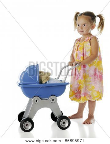 A pretty, barefoot preschooler pushing her rag doll
