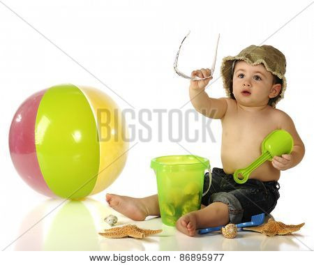 An adorable baby boy in rolled up jeans and hat handing off his sunglasses as he sits among sea shells and beach toys.  Isolated on white.