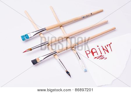 Paint word on a white sheet and paint brushes